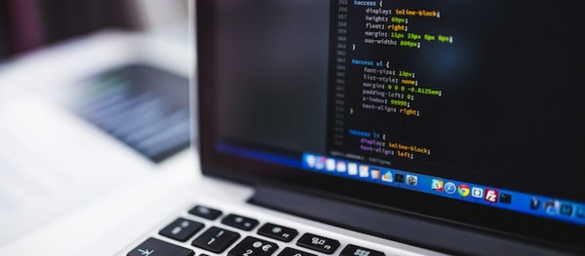 web designer coding on laptop